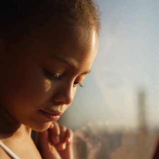 Close up of a little girl looking out a window